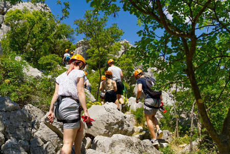 Hiking - Adventure - Healthy lifestyle. Group of hikers walks on mountain rural landscape. Group of active people walking, multiracial hikers walking along the forest path. Tourists with backpacks hiking on footpath through the woods at mountain. Banque d'images