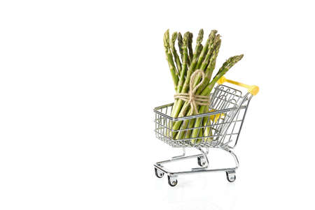 Organic fresh green asparagus in shopping cart isolated on white background. vegetable garden asparagus Banque d'images