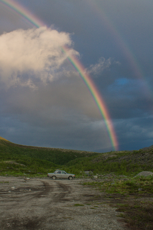 Khibiny Mountains with a cloudy sky and a rainbow