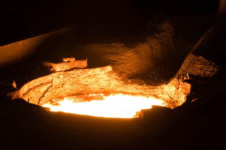 slack: Closeup of hot liquid metal in a furnace