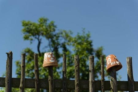 flowerpots: Decorated flowerpots on a simple wooden fence