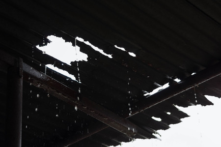 roof: Rain pouring through a leaky tin roof Stock Photo