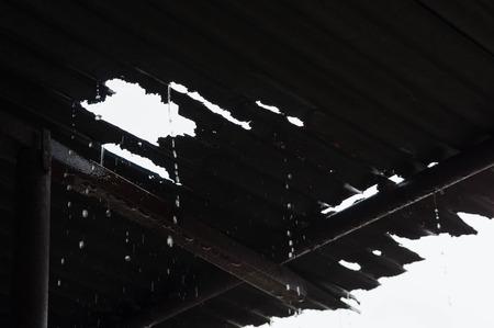 Rain pouring through a leaky tin roof Stock Photo