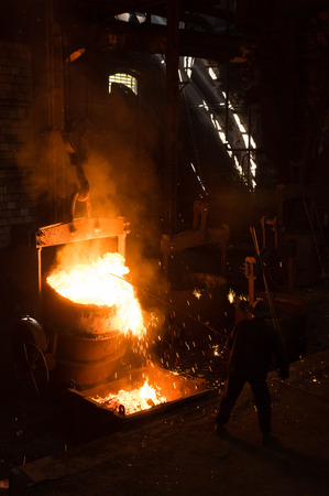 removing: Foundry worker removing slack from hot liquid metal