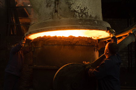 manipulating: Foundry workers manipulating with hot liquid metal Stock Photo
