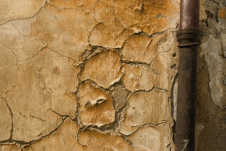 gutter: Cracked plaster of beige wall with gutter pipe