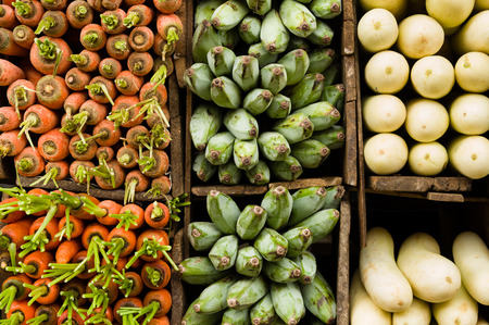 neatly: Several varieties of tropical vegetables neatly arranged for sale