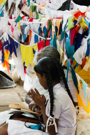 reciting: Grandmother and granddaughter praying at buddhist temple Stock Photo