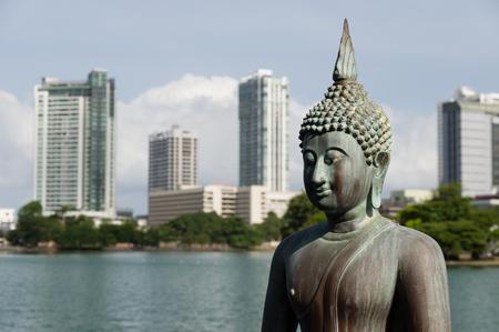 gautama: Gangaramaya temple Buddha statues with the city of Colombo in background Stock Photo