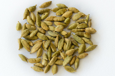 cardamum: Heap of dry green cardamons on a white background