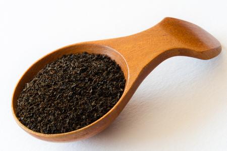 pekoe: Isolated wooden spoon with Ceylon BOP tea on white background
