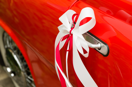 Red and white decorative wedding ribbons on a door handle of a red vintage car Reklamní fotografie