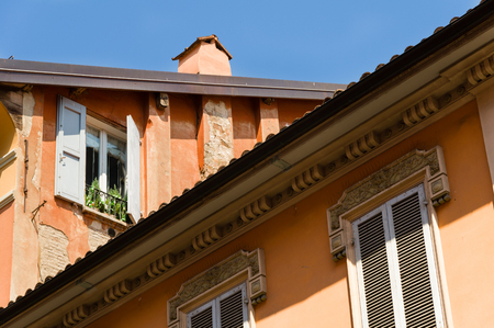 Orange facade of house with wooden window shutters in Bologna