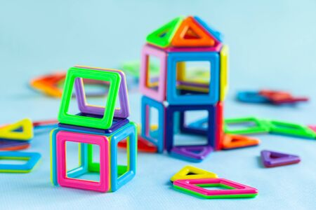 Concept of interesting educational games for little children. Magnetic constructor to play at home during quarantine. Fine motor skills, reativity developing, learning colors, shapes. Blue background