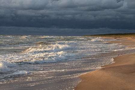 Sunset over sandy beach and dark blue sky before the storm. Stock Photo