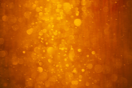 Orange - red - yellow background. It is photo of snow fall in night in lantern light. This blurred snowing in warm colors can be a Christmas or winter background texture.