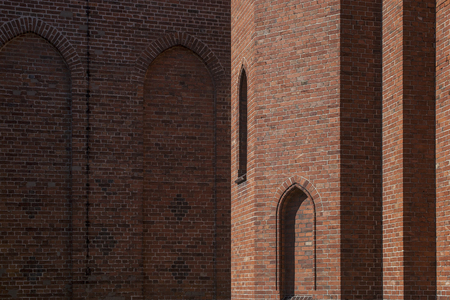 Half light and half shadow wall of church with gothic style arches in window niches. Red bricks wall texture for background. Stock Photo