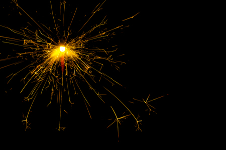 sparklet: New year and Christmas sparkler on black background. Space for text.