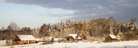 Sunny winter panorama of farm, fields and forests. A snowy wintertime scene of countryside houses. Christmas mood landscape.
