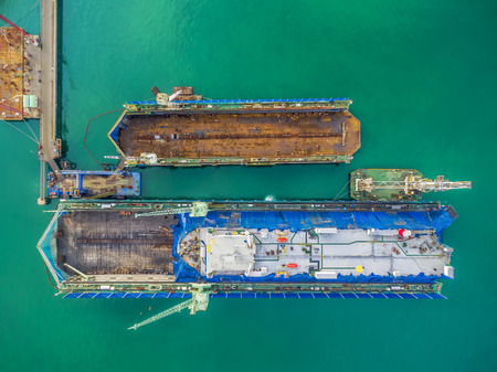 shipbuilding: aerial view shipyard have crane machine and container ship in green sea . Stock Photo
