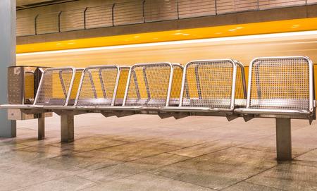 u bahn: Yellow Train speeding in subway behind metal waiting benches