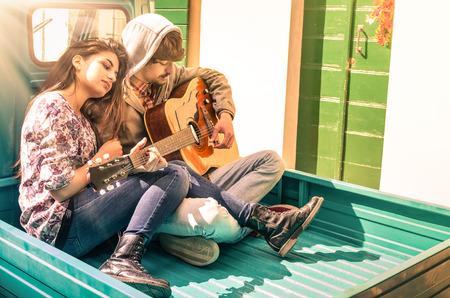 uomo sotto la pioggia: Romantico giovane coppia di innamorati che giocano chitarra all'aperto con sunshines dopo la pioggia