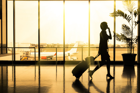 traveller: Business woman at Airport - Silhouette of a passenger