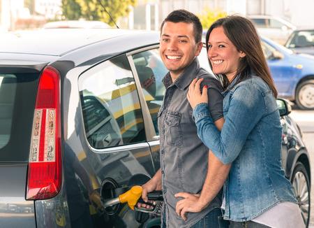 若い男の肖像画と現代の車のガソリン タンクを埋める男の女性ポンプ用ガスでポンピング ガソリン燃料ステーションで幸せなカップル