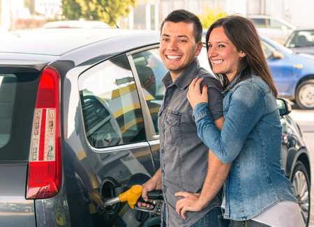 gasolinera: Pareja feliz en la estaci�n de combustible de bombeo de gasolina en la bomba de gas Retrato de hombre joven y de la mujer del hombre llenando coche moderno en el tanque de la gasolina