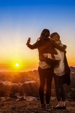 Pareja de mujeres jóvenes mejores amigos tomando un selfie durante la puesta de sol en el Twin Peaks en San Francisco - las muchachas del adolescente que se divierten juntos al aire libre