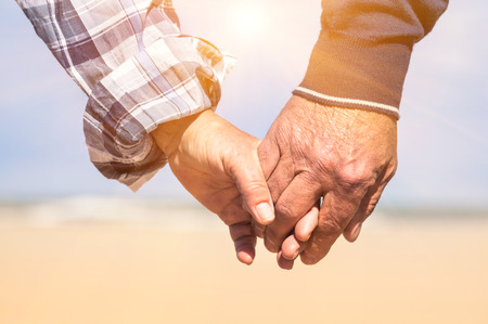 Senior couple in love walking at the beach holding hands in a romantic sunny day - Concept of love and family union photo
