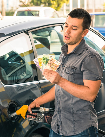 fueling: Man at gasoline station - Troubles dealing with money for rising gas prices
