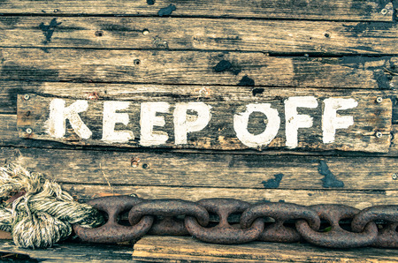 stay at the course: Keep Off sign - Wooden painted background - Vintage filtered look Stock Photo