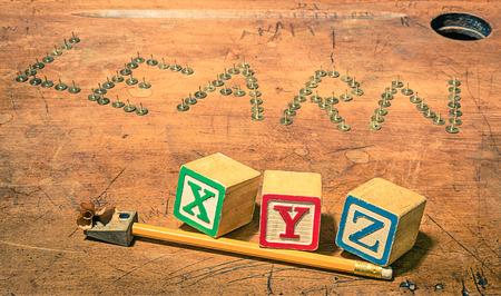 temperino: Banco di scuola dell'annata con la composizione di matita temperino e baby cubi lettere - Nozione di studio e di apprendimento