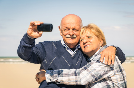 Senior happy couple taking a selfie at the beach during spring waiting for the summer - Concept of elderly and interaction with new technologies and trends photo