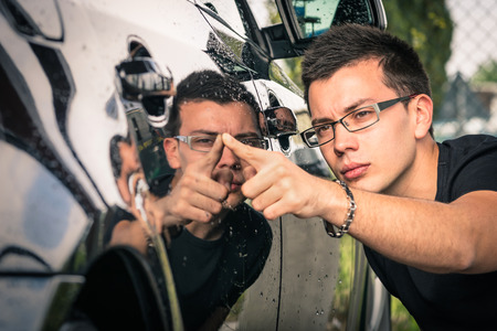 carwash: Hombre joven con gafas de la inspección de un automóvil de lujo antes de que un comercio de segunda mano