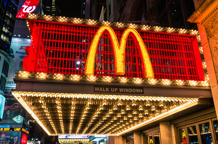 42nd: NEW YORK - NOVEMBER 22, 2013  illuminated neon sign with the world famous  M  representing McDonalds along 42nd street in Times Square  The company was founded in 1940 in San Bernardino, California  Editorial