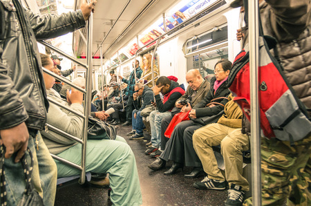 manhattan mirror new york: NEW YORK - NOVEMBER 2, 2013  mixed people in the subway, downtown Manhattan  The trains are the places where the most mixed melting pot in the world take place, and the real mirror of actual society  Editorial