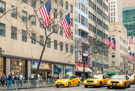 taxicabs: NEW YORK - DECEMBER 22, 2013  yellow taxicabs and american flags on the 5th Avenue, named  The most expensive street in the world  at the crossroad with West 48th Street in Midtown Manhattan
