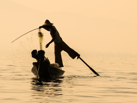 Traditional burmese fisherman balancing on the paddle while recovering the fishing net photo