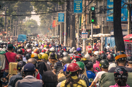 cramped: HO CHI MINH CITY, VIETNAM - FEBRUARY 2, 2013  traffic jam with a congestion of scooters and people with colorful helmets  There are approximately 340,000 cars and 3,5 million motorcycles in the city