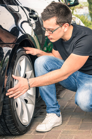 Young man with glasses inspecting a tire of a luxury car before a second hand trade photo