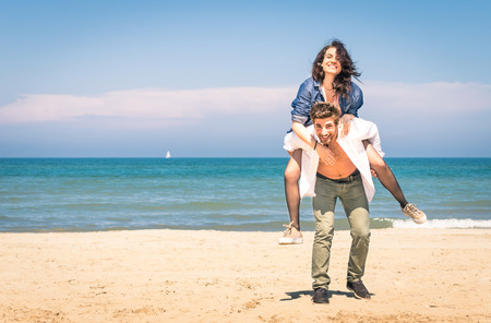 piggy back: Young couple playing at the beach having fun with a piggyback jump - Happy man and woman at the beginning of a love story Stock Photo