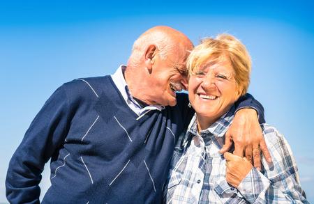 Couple de personnes âgées heureux dans l'amour pendant la retraite - le mode de vie des personnes âgées joyeux avec l'homme chuchotant et souriant avec sa femme