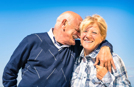 active retirement: Happy senior couple in love during retirement - Joyful elderly lifestyle with man whispering and smiling with her wife Stock Photo