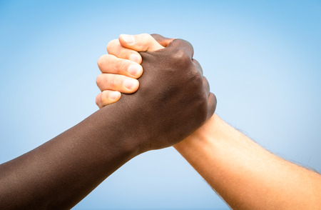 racism: Black and white human hands in a modern handshake to show each other friendship and respect - Arm wrestling against racism
