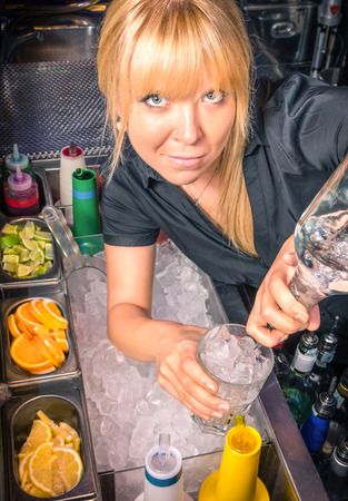 bartend: Beautiful blonde Barmaid at Work pouring a cocktail in a mixing Glass