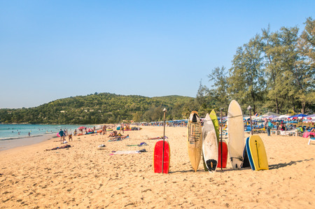 Surfboards at a tropical beach - Extreme sport body boards in a sunny day with unrecognizable generic people relaxing at the seaside