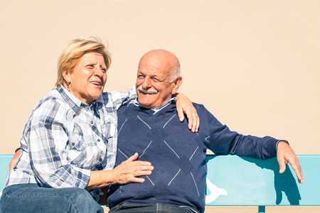 Happy senior couple in love having fun at the beach - Joyful elderly lifestyle with man and her wife laughing outdoors on a bench photo