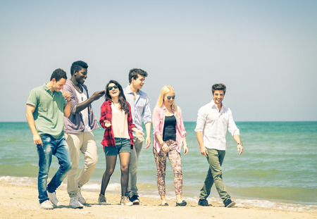 Group of happy friends walking a talking at the beach - Concept of international multiracial friendship - Retro nostalgic filtered look photo